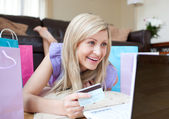 Smiling woman shopping online lying on the floor — Stock Photo