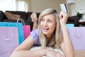 Joyful woman holding a credit card after shopping — Stock Photo