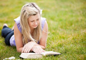 Beautiful woman reading a book in a park — Stock Photo