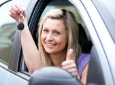 Lively female driver showing a key after bying a new car — Стоковое фото