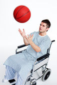 Patient in wheelchair playing with a basket ball — Stockfoto