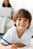 Smiling little boy drawing lying on the floor — Stock Photo