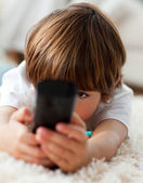 Adorable little boy holding a remote lying on the floor — Stock Photo