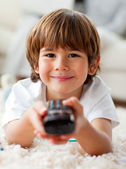 Smiling little boy watching TV lying on the floor — Stock Photo