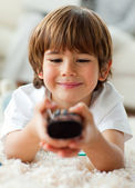Cute little boy holding a remote lying on the floor — Stock Photo