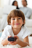 Adorable little boy watching TV lying on the floor — Stock Photo