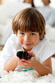 Smiling little boy holding a remote lying on the floor — Stock Photo