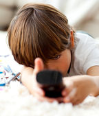 Cute little boy watching TV lying on the floor — Stock Photo