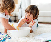 Cute children eating chips and drawing — Stock Photo
