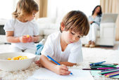 Happy children eating chips and drawing — Stock Photo