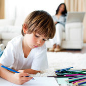 Concentrated little boy drawing and his sister eating chips — Stock Photo