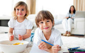 Smiling siblings eating chips and drawing — Stock Photo