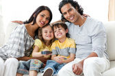Cheerful family watching TV together — Stock Photo