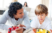 Father and his son playing video games lying on the floor — Stock Photo