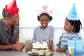 Smiling little girl and her family celebrating her birthday — Stock Photo
