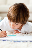 Serious little boy drawing lying on the floor — Stock Photo