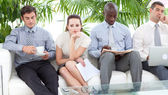 Bored business sitting on a sofa waiting for an interview — Stock Photo