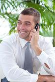 Businessman sitting on sofa and talking on phone — Stock Photo