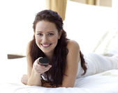 Beautiful woman in bedroom holding a remote control — Stock Photo
