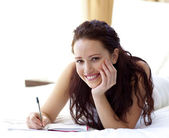 Beautiful woman writing notes in bed — Stock Photo