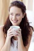 Beautiful woman drinking a cup of coffee in bed — Stock Photo