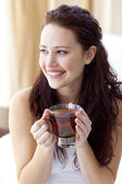 Beautiful woman drinking a cup of tea in bed — Stock Photo