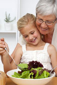 Happy grandmother cooking a salad with granddaughter — Foto de Stock