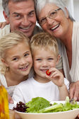 Happy grandparents eating a salad with grandchildren — Stock Photo