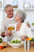 Senior couple in love eating a salad in the kitchen — Stock Photo