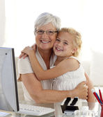 Granddaughter and grandmother hugging and using a computer — Stock Photo