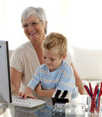 Grandson using a computer with his grandmother — Stock Photo