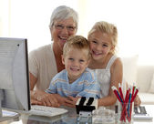 Happy children using a computer with their grandmother — Stock Photo