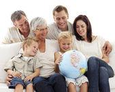Grande família no sofá a olhar para um globo terrestre — Foto Stock
