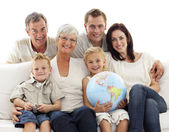 Big family on sofa holding a terrestrial globe — Stock Photo