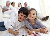Дети живопись на этаже с их семьей в диван — Стоковое фото