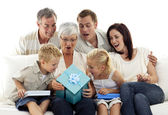 Family giving a present to grandmother — Stockfoto