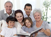 Smiling family looking at a photograph album — Stock Photo