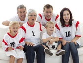 Excited family watching a football match in television — Stock Photo