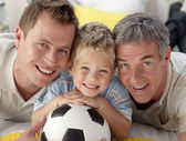 Portrait of smiling son, father and grandfather on floor — Foto de Stock