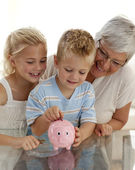 Close-up of grandmother and children saving money — Stock Photo
