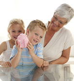 Grandmother and children saving money — Stock Photo