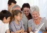 Family giving a present to the grandmother — Stock Photo