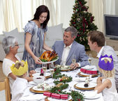 Happy family celebrating Christmas dinner with turkey — Stock Photo