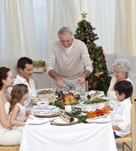 Family celebrating Christmas dinner with turkey at home — Stock Photo