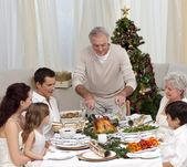 Family having Christmas dinner eating turkey — Stock Photo
