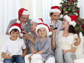 Family celebrating Christmas with wine and sweets at home — Stock Photo