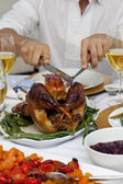Close-up of a man cutting a turkey for Christmas dinner — Stok fotoğraf