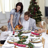 Parents and children in Christmas dinner with turkey — Stock Photo