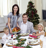 Parents and children celebrating Christmas dinner with turkey — Stock Photo