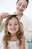 Portrait of mother doing her daughter's hair — Stock Photo